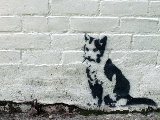 Stencil of a cat on a brick wall.